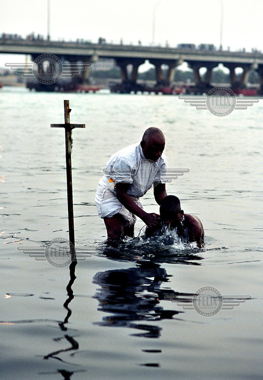 ©Sven Torfinn/Panos Pictures ..Benin, Cotonou, 2002.boy is baptised in the river by a priest with a cross, in the background a bridge..members the 'eglise celeste' (celestial church), where they practise an kind of Christianity that has adopted African elements, tradition, culture, they for instance tolerate polygamy..sect, religion, belief..