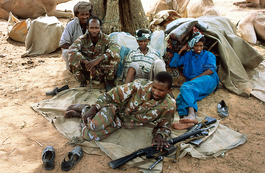 Sudan. West Darfur. Habilah. On sunday is market day. A group of nomads, belonging to the arab milicia called Janjaweed, came in the village. They rest under a tree during the hot hours of the day. Two men are dressed with military outfits. The kalashnikov are lying on the ground. © 2004 Didier Ruef