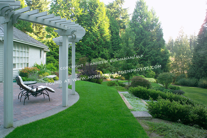 The edge of a decorative brick patio topped by a curving arbor, and a comfortable lounge chair look off the rear of this suburban home near Seattle which opens to a large, well-groomed backyard with an expanse of grass on a slope, and surrounded and interesected with beds and borders of mixed trees and shrubs in a typical Northwest summer garden scene.