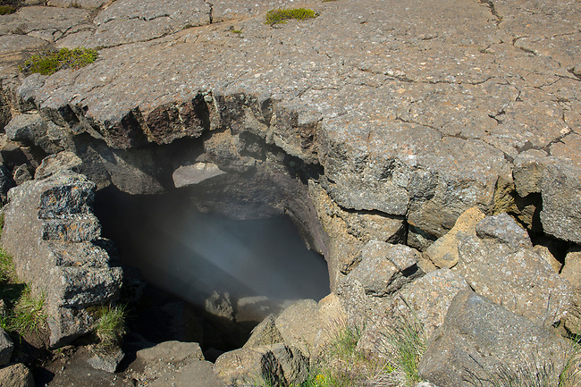 Steam rising from Grjotagja, a small lava cave near Lake Myvatn with a thermal spring inside in Northeast Iceland.