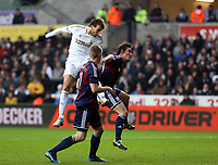 Saturday 19 January 2013<br /> Pictured: Michu of Swansea (TOP) heads the ball off target while closely guarded by Ryan SHawcross (FRONT) and another Stoke player<br /> Re: Barclay's Premier League, Swansea City FC v Stoke City at the Liberty Stadium, south Wales.