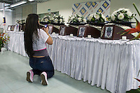 A woman records pictures and coffins of the nine skeletal presented to their families by The Attorney General's Office in Medellin,. The exhumations Were Conducted in the Departments of Antioquia, Risaralda and Meta., Colombia, 20/04/2012. Photo by Fredy Amariles / viewpress.