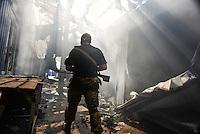Pro-Russian rebel walks by line of shops burned and destroyed by shelling. Donetsk, Eastern Ukraine