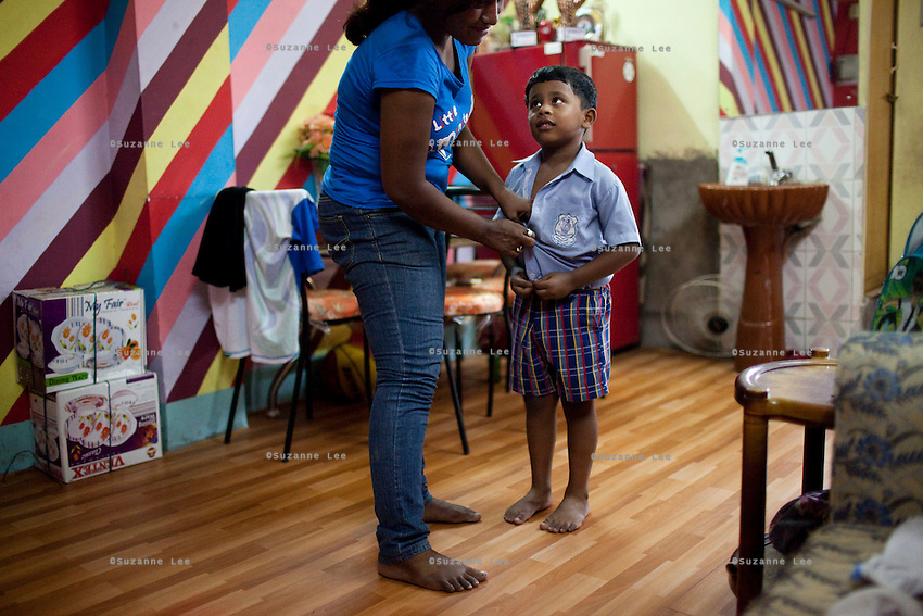 Razia Shabnam (in blue) undresses her son for a shower at home in Ekbalpore, Calcutta, West Bengal, India. Razia Shabnam, 28, was one of the first women boxers in Kolkata. She was also the first woman in her community to go to college. She is now a coach and one of only three international female boxing referees in India.  Photo by Suzanne Lee for Panos London