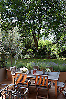 A teak table and chairs on the deck overlooking the garden