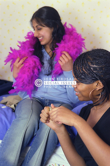 Two teenage girls; one wearing pink feather boa; sitting in bedroom smiling,