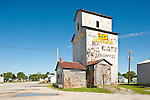 Rusted metal grain elevator, with cafe advertisement painted on the side.