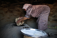 "A woman bakes bread in Jenba a Palestinian town of 50 families seats in an area called by the IDF as ""Firing Zone 918"" and is located in the southern Hebron hills near the town of Yatta.  Spread over 30,000 dunams, it includes twelve Palestinian villages.  According to OCHA figures, 1,622 people lived in the area in 2010, and according to local residents the number of inhabitants currently stands at about 1,800. For over a decade, the residents of twelve uniquely traditional Palestinian villages in the area of Masafer-Yatta in the south Hebron hills have lived under the constant threat of demolition, evacuation, and dispossession.<br />