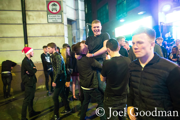 "© Joel Goodman - 07973 332324 . 23/12/2017. Manchester, UK. Revellers out on Withy Grove outside the Printworks in Manchester City Centre overnight during "" Mad Friday "" , named for being one of the busiest nights of the year for the emergency services in the UK . Photo credit : Joel Goodman"