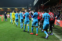 The two teams enter the field of play ahead of kick-off during Brentford vs Barnet, Emirates FA Cup Football at Griffin Park on 5th February 2019