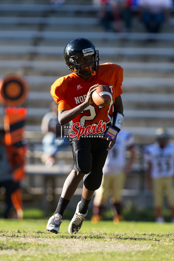 Ahmadeus Kluttz (23) of the Northwest Cabarrus Titans runs with the football against the Winkler Wolves in 7th grade football action at Trojan Stadium October 7, 2014, in Concord, North Carolina.  The Titans defeated the Wolves 58-30.  (Brian Westerholt/Sports On Film)
