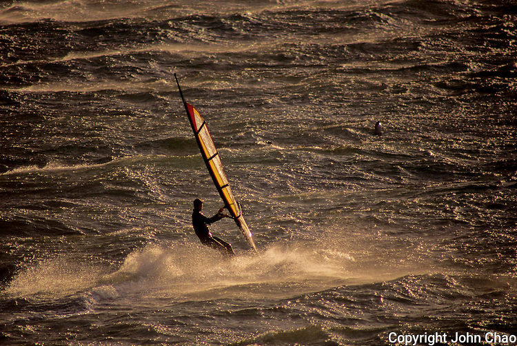 Silhouetted sailboarder on Puget Sound off Alki Point, Seattle, Washington State