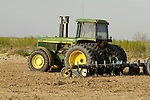 1990 John Deere 4555 tractor with tined harrow in a field, Dawson Co., Texas