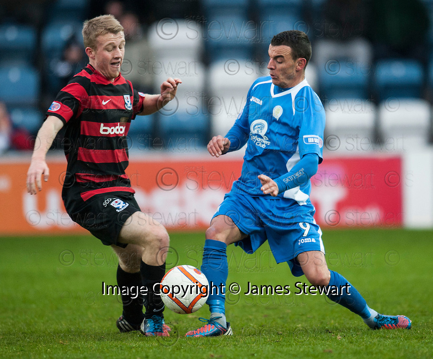 Ayr Utd's Robbie Crawford and Queen of the South's Derek Lyle challenge for the ball.