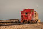 Santa Fe railroad caboose at the end of a line of mineral hopper cars, Boron, Calif.