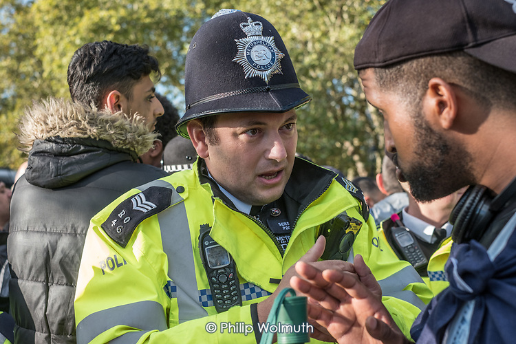 Police intervene in a heated debate between Muslims and islamophobic Tommy Robinson supporters, before escorting a speaker out of the park.  Speakers' Corner, Hyde Park, London.