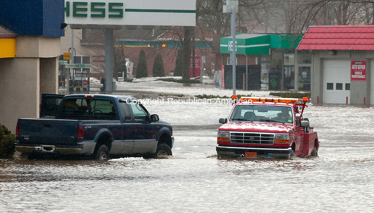 NEW MILFORD, CT, 07 MARCH 2011-030711JS01--A tow truck driver makes his way throught the flooded parking lot at Southworth Sales and Service on Danbury Road (Route 7) in New Milford on Monday. The recent heavy rain and melting snow caused the Houstaonic River to overflow forcing officals to close a portion of Route 7 near Bridge Street (Route 202). <br /> Jim Shannon/Republican-American