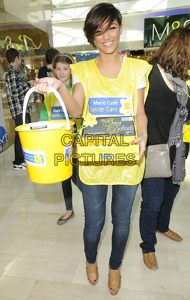 THE SATURDAYS (Frankie Sandford ) .At the Marie Curie Cancer Care's Great Daffodil Appeal, Westfield, London, England, UK, 12th March 2011..full length yellow vest bucket collecting charity  jeans brown tan platform wedges .CAP/CAN.©Can Nguyen/Capital Pictures.