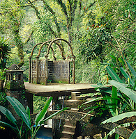 A classical ruin made of weathered concrete is situated on a raised platform in the centre of the overgrown garden