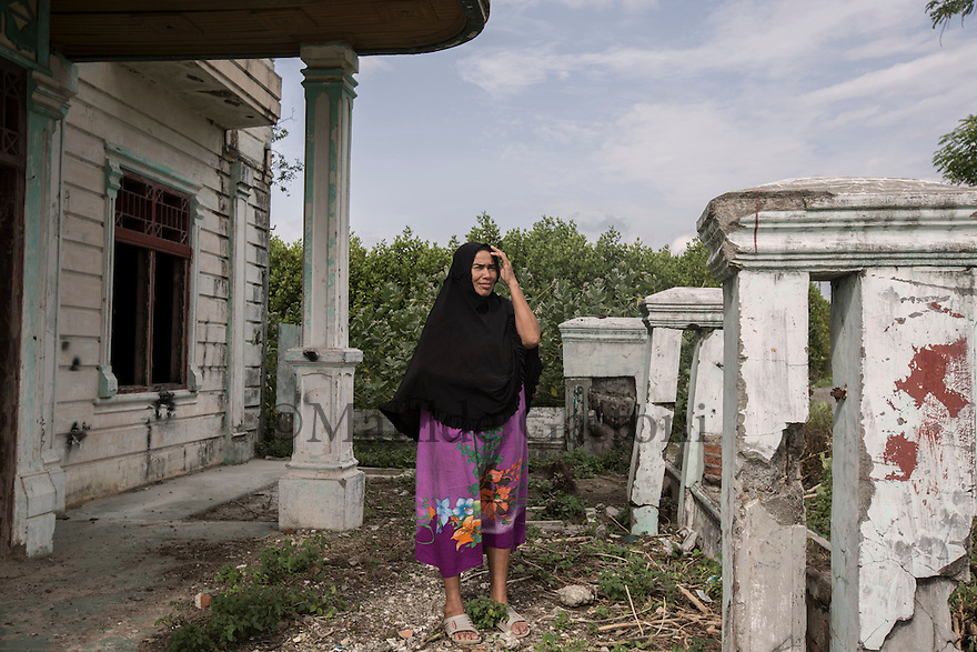 """Indonesia – Sumatra – Banda Aceh – Lampaseh – Yasmanidar, 60-year-old stands in what is left of a villa destroyed by the tsunami in her neighborhood. """"The second wave smashed me on the ground, the third brought me up"""", she explains calmly. Yasmanidar lost her husband and thirty other family members during the disaster. Carried away for several kilometres by a black and muddy water full of sharp debris, Yasmanidar ended up on the second floor of a building, through a hole in the wall. There, she managed to climb on the roof, where she spent several hours waiting for help. """"I was seeing people carried away by the water, corpses without head and limbs... A lot of people were crying for help, but I couldn't do anything"""" she remembers."""