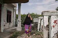 "Indonesia – Sumatra – Banda Aceh – Lampaseh – Yasmanidar, 60-year-old stands in what is left of a villa destroyed by the tsunami in her neighborhood. ""The second wave smashed me on the ground, the third brought me up"", she explains calmly. Yasmanidar lost her husband and thirty other family members during the disaster. Carried away for several kilometres by a black and muddy water full of sharp debris, Yasmanidar ended up on the second floor of a building, through a hole in the wall. There, she managed to climb on the roof, where she spent several hours waiting for help. ""I was seeing people carried away by the water, corpses without head and limbs... A lot of people were crying for help, but I couldn't do anything"" she remembers."