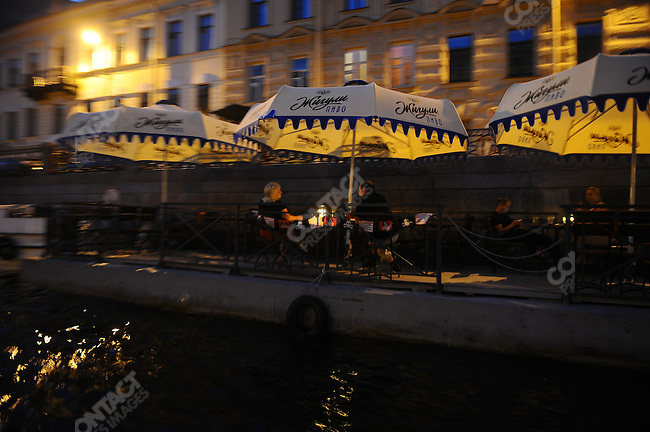 On a dock on the river Moika people enjoyed drinks after midnight, White Nights, St. Petersburg, Russia, July 8, 2010