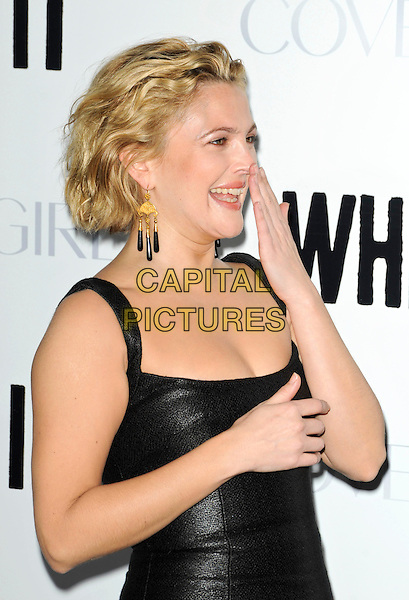 "DREW BARRYMORE .Attending the ""Whip It"" Los Angeles Premiere held At Grauman's Chinese Theatre, Hollywood, California, USA, 29th September 2009..half length black dress shiny leather  sleeveless  director earrings gold dangly side hand smiling laughing profile .CAP/ROT.©Lee Roth/Capital Pictures"