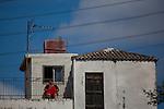 Woman in red dress asleep in the sun, Chania, Crete.
