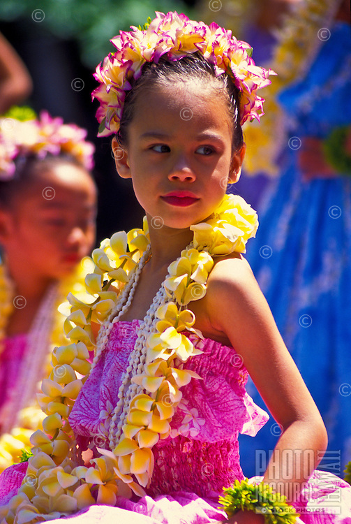 Young girl wearing plumeria lei at a hula performance.