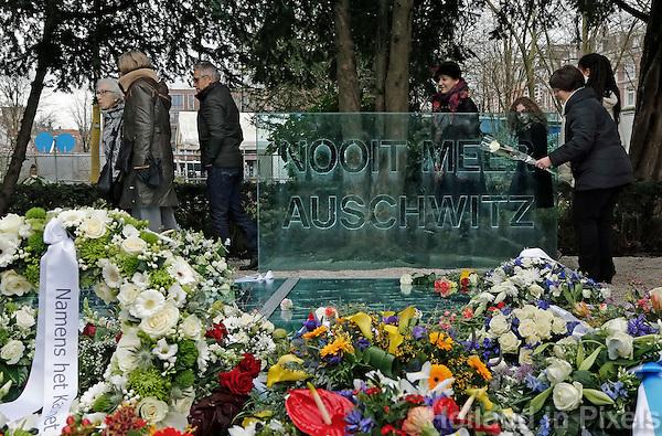 Nederland Amsterdam 3016 01 31.  Jaarlijkse Auschwitzherdenking in het Wertheimpark. Mensen leggen bloemen op het spiegel monument van Jan Wolkers