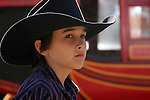 A young cowboy in a black hat standing in front of the Butterfield Stage Coach in Texas