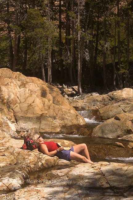 Woman hiker relaxing on the rocks next to Canyon Creek, Tahoe National Forest California