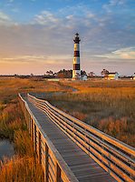 Cape Hatteras National Seashore, North Carolina: Sunrise lights the Bodie Island lighthouse (1872) and boardwalk on North Carolina's Outer Banks