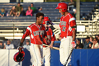 Batavia Muckdogs third baseman Mason Davis (7) celebrates with Kevin Grove (12) after scoring a run during a game against the Mahoning Valley Scrappers on June 21, 2014 at Dwyer Stadium in Batavia, New York.  Batavia defeated Mahoning Valley 10-6.  (Mike Janes/Four Seam Images)