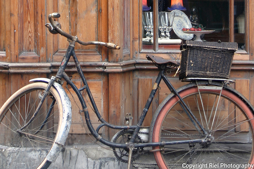 An old bicycle juxtaposed with finer items in a French gift shop window in Honfleur,France