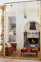 Sitting room with lit fire reflected in a gilt framed mirror, Loughcrew House, County Meath, Ireland