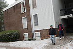 December 16, 2010. Raleigh, NC.. Khem Khadka, Mr. Mishra's roommate, center, and TP Mishra, right, make their way into the parking lot of the apartment complex. Mr. Mishra will drive Mr. Khadka to work because of the bad weather, he has been driving for just over a month.. TP Mishra, a refugee from Bhutan, has recently relocated from the Bronx to Raleigh, where he lives in an suburban apartment  with his wife, as well as another Bhutanese couple.