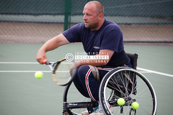 Disabled man playing wheelchair tennis in an adapted wheelchair at the Nottingham tennis centre,