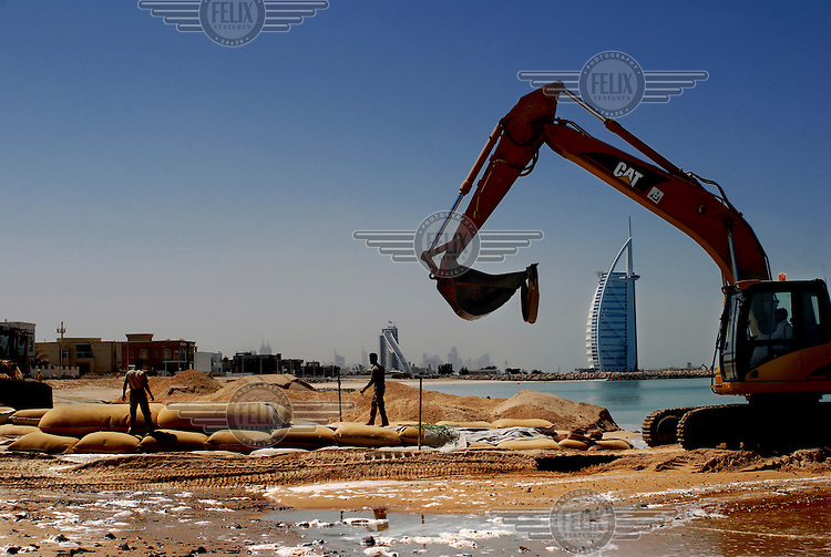 Migrant labourers working on extending the Dubai beach, close to the Burj Al Arab Hotel (right). The employers keep their employee's passports when they arrive and pay their workers around 150 Euros a month.