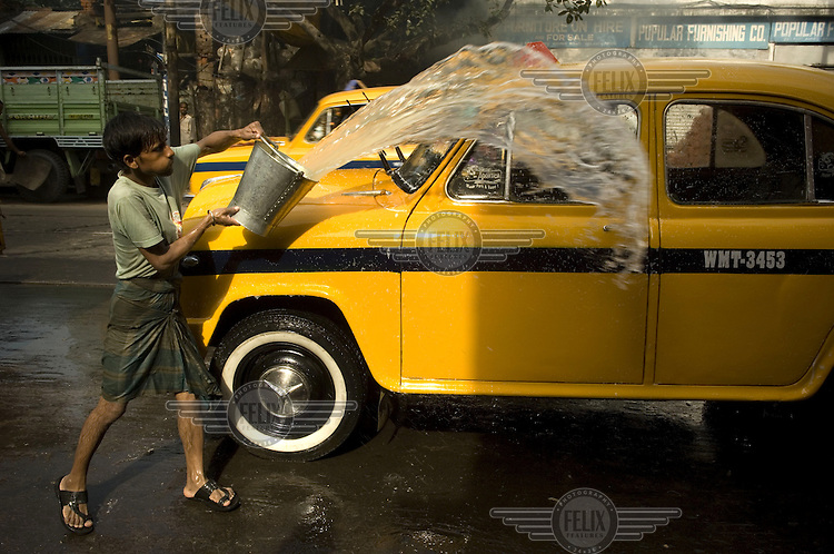 A man washes a taxi in Kolkata.