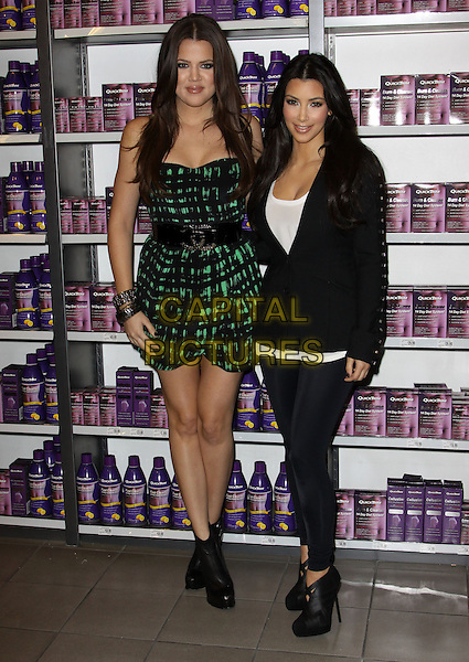 "KHLOE KARDASHIAN & KIM KARDASHIAN.At a photocall to introduce ""Quicktrim"" held At GNC Beverly Center, Los Angeles, California, USA,.15th October 2009..full length sisters family strapless green and black print dress waist belt tall short jacket leggings ankle boots heels ribbon woven silk satin white top bracelets studs studded .CAP/ADM/KB.©Kevan Brooks/Admedia/Capital Pictures"