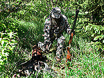 Wild turkey hunter in camouflage clothing using turkey call
