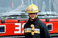 Firefighter in firekit stood in front of a fire engine. He is wearing a fire helmet, fire tunic and leggings and fireboots. On his tunic is a right angled intrinsically safe torch...© SHOUT. THIS PICTURE MUST ONLY BE USED TO ILLUSTRATE THE EMERGENCY SERVICES IN A POSITIVE MANNER. CONTACT JOHN CALLAN. Exact date unknown.john@shoutpictures.com.www.shoutpictures.com..