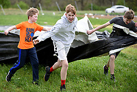 NWA Democrat-Gazette/DAVID GOTTSCHALK Max Sherwood (center), an eighth grade student at The New School, moves plastic tarps Thursday, April 11, 2019, with other seventh and eighth grade students from the school during a service project at Cobblestone Farms in Fayetteville. Cobblestone Farms is a non profit that donates half of the food grown to food insecure families in the northwest Arkansas area.