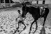 A boy walks an Arabian pure breed horse, named Rawnaq afer training at a stable in the neighborhood of Essawiya on June 07, 2016 in East Jerusalem. <br /> Photo Daniel Berehulak for the New York Times