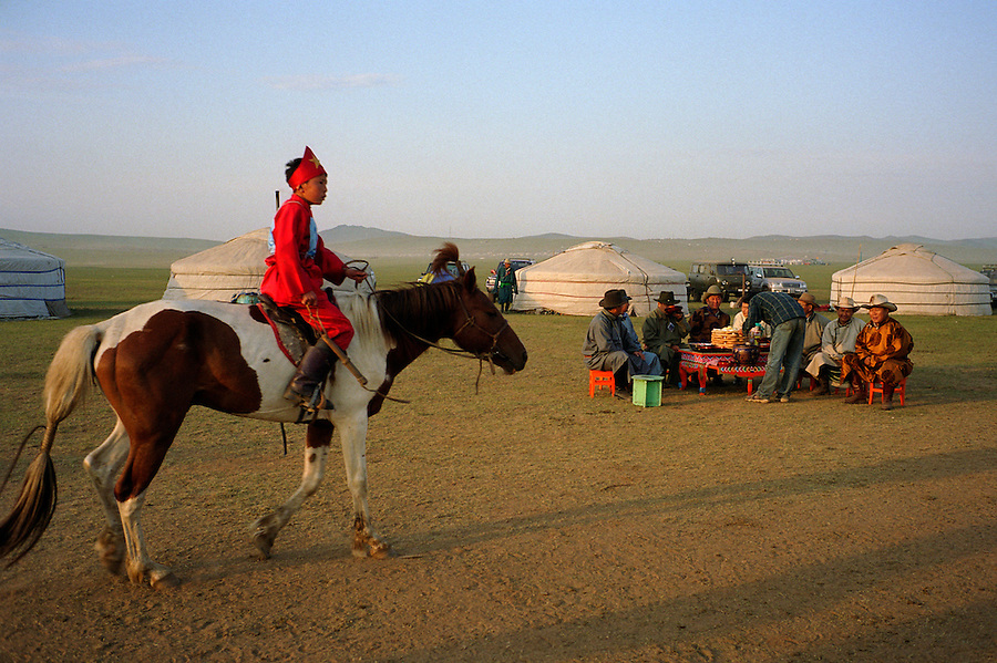 Khui Doloon Khudag, Mongolia, July 2003..Competitors & spectators at the horse racing in the national Naadam 40 kilometres outside Ulaanbaatar..Owners & coaches watch their jockeys parade their horses before the race, in a ritual where the jockey praises his horse by singing serenades while circling the owner's other horses.