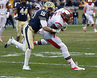 Pitt defensive back Jarred Holley (18) tackles Rutger wide receiver Tim Wright. The Pitt Panthers defeat the Rutgers Scarlet Knights 27-6 on Saturday, November 24, 2012 at Heinz Field , Pittsburgh, PA.