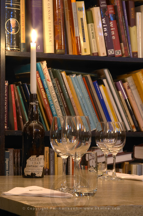 The wine book library with a table with tasting glasses and a candle in a wine bottle at the wine cellar storage company Grappe in Stockholm where private individual s can store and age wine bottles. Källaren Grappe Wine Storage Cellar, Stockholm, Sweden, Sverige, Europe