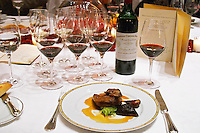 Dinner in the George V luxury restaurant in Paris. Grilled dove and Chateau Cheval Blanc 1989 wine. Paris, France. Wine tasting. Wine glasses.