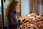 Woman picking fresh produce from a vegetable stall at a farm market grocery store Canada